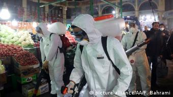 Fire fighter teams with protective suits disinfect the Tajrish Bazaar a (picture-alliance/AA/F. Bahrami)
