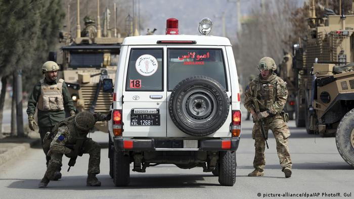 British security forces respond to the Kabul gun attack, taking cover behind an armoured jeep