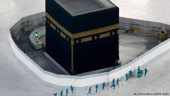 The imposing black square building of the Kaaba sits in the center of the Grand Mosque in Mecca while a line of seemingly tiny men in green sanitation uniforms clean the usually busy floor of white tiles