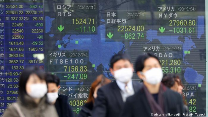 People walk in front of sign showing stock markets (picture-alliance/Jiji Press/M. Taguchi)