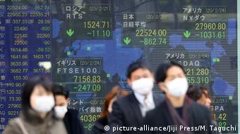 People in masks with a stock exchange board behind them