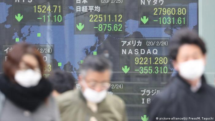 Passersby wearing face masks walk past a stock indicator board showing the world's major stock indices in Tokyo