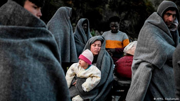 People wrapped in thick grey blankets stand while a woman in a blanket sits with a baby on her knee