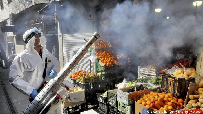 A worker disinfects a market in Tehran