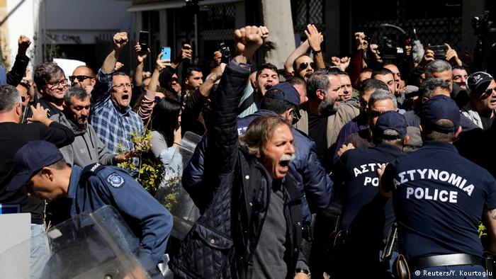Protesters push back against police at a crossing in Nicosia