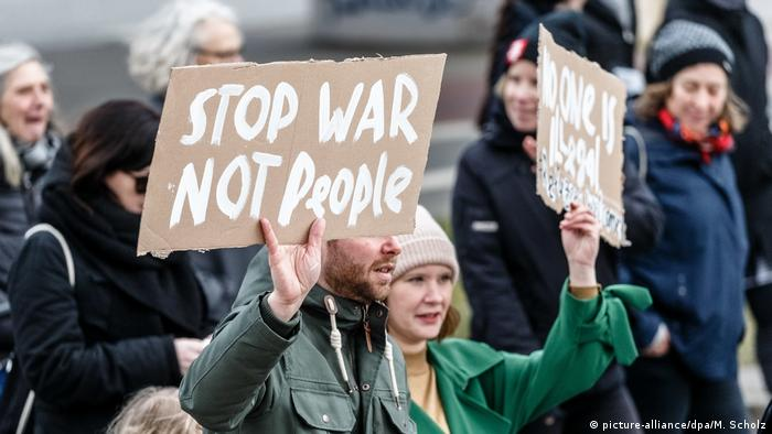 A man with a sign reading Stop war, not people. (picture-alliance/dpa/M. Scholz)