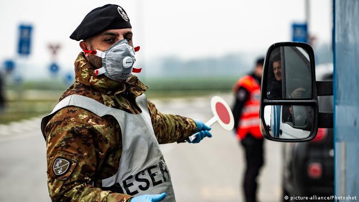 Итальянский военнослужащий останавливает машину для контроля