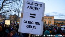 08.03.2019, Niedersachsen, Hannover: Eine Frau hält bei einer Demonstration am Weltfrauentag ein Plakat mit der Aufschrift Gleiche Arbeit - gleiches Geld. Foto: Christophe Gateau/dpa | Verwendung weltweit