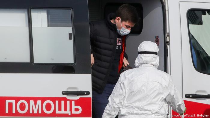 Человек в маске выходит из машины скорой помощи навстречу врачу