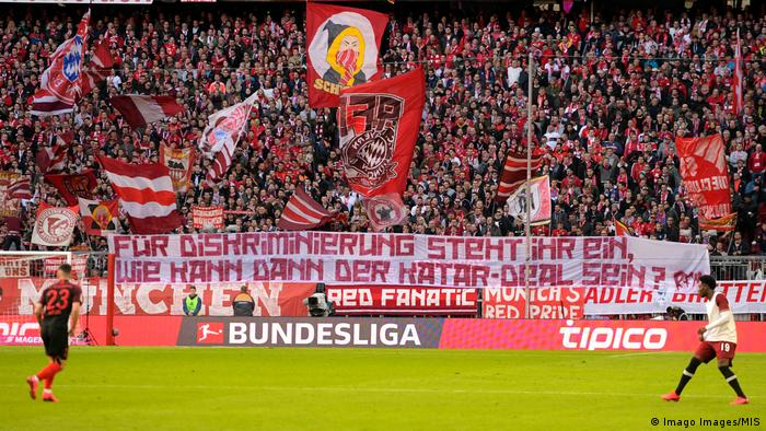 Bayern Munich fans hold up a banner critical of their club's dealings with Qatar