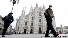 A man wearing a face mask walks past Piazza Duomo square after the government decree to close cinemas, schools and urge people to work from home and not stand closer than one metre to each other, in Milan, Italy, March 5, 2020. REUTERS/Guglielmo Mangiapane