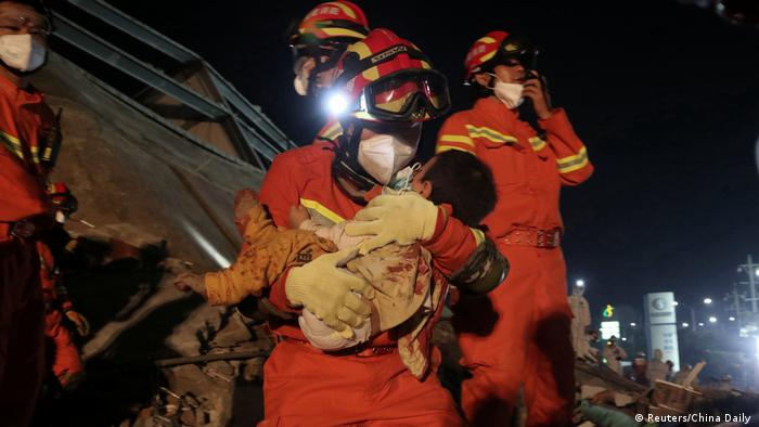 A worker wearing a face mask rescues a child at the site where a hotel being used to quarantine people collapsed