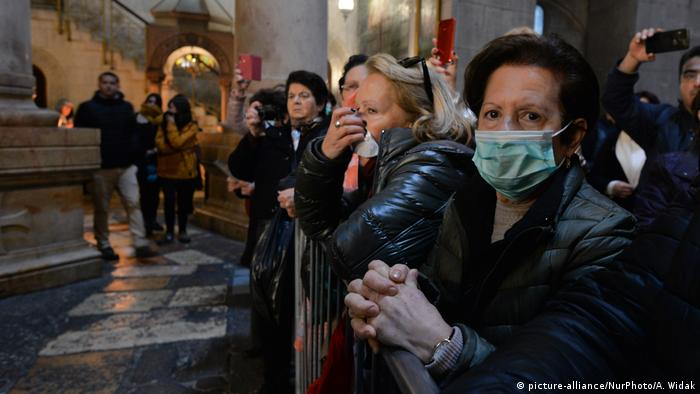 People wearing masks are seen inside the Church of the Holy Sepulchre in Jerusalem's Old City (picture-alliance/NurPhoto/A. Widak)  - 52685426 401 - Coronavirus updates: WHO praises Italy for its 'genuine sacrifices'  - 52685426 401 - Coronavirus updates: WHO praises Italy for its 'genuine sacrifices'
