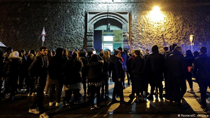 Concentração de parentes de presos diante de prisão Poggioreale, em Nápoles, em foto noturna