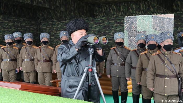 Munido de binóculos, líder norte-coreano, Kim Jong-un supervisiona exercícios com mísseis em fevereiro de 2020