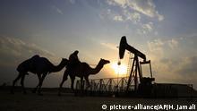 Ölpumpe im Sonnenlicht und Mann mit Kamelen davor