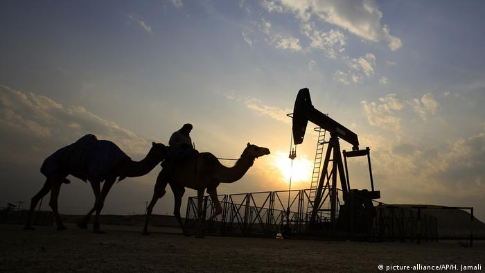 A man rides a camel through the desert oil field