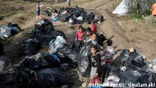 Children help clean the makeshift migrant camp after a rainfall hit the island of Chios on December 11, 2019 where thousands of refugees and migrants live in squalid condition, without water and electricity while winter has started. - Officials on the three Greek islands hosting the country's largest migrant camps staged a walkout on December 11 to reject plans for larger facilities in an ongoing dispute with the government. - According to government figures, there are over 40,000 asylum-seekers on the islands,in addition to over 20,000 people in camps on the mainland, which are nearly full or already past capacity.Hundreds more arrive daily. (Photo by LOUISA GOULIAMAKI / AFP) (Photo by LOUISA GOULIAMAKI/AFP via Getty Images)