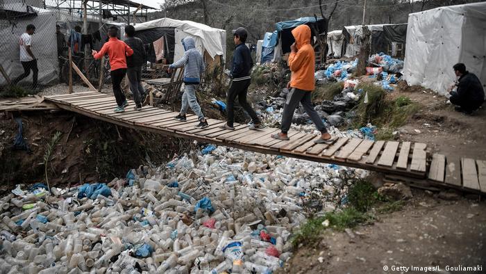 Children walk over a bridge in the Moria migrant camp