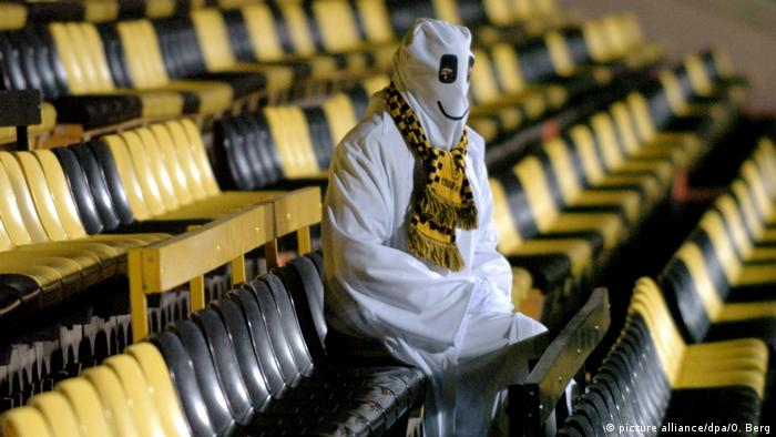 A fan dressed as a ghost sits alone in a stadium