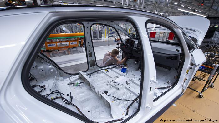 A worker completes an electric car body at the assembly line at the plant of the German manufacturer Volkswagen AG (VW) in Zwickau, eastern Germany