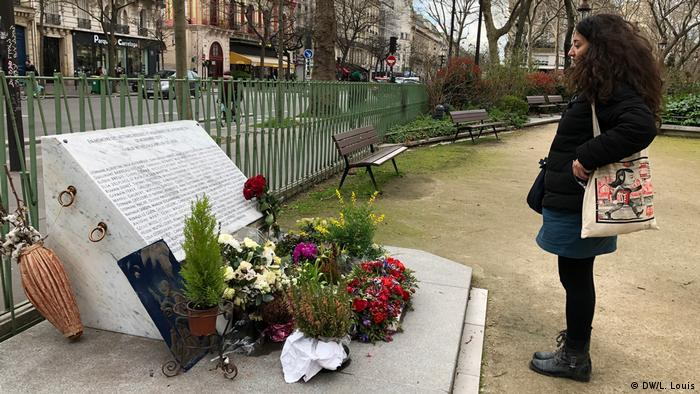 Catherine Bertrand stands in front of a memorial to the people killed in the 2015 Paris attacks