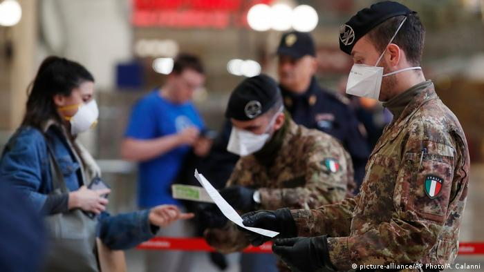 Soldados con ropa de camuflaje y máscaras de respiración controlan a los pasajeros en una estación de tren.