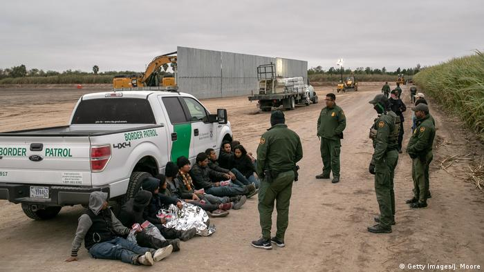 US Border Patrol agents detain undocumented immigrants caught near a section of privately-built border wall under construction on December 11, 2019 near Mission, Texas
