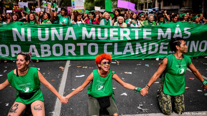 Women take part in a women's strike to demand the legalization of abortion, gender equality and the end of violence against women, in front of the Congress in Buenos Aires, on March 9, 2020. A banner in the background in Spanish reads, Not one more death or clandestine abortion.