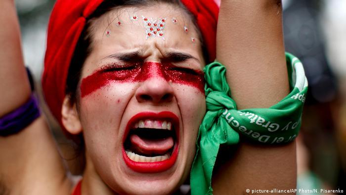 Una mujer con la boca abierta, los ojos cerrados, y un pañuelo verde en un brazo levantado.