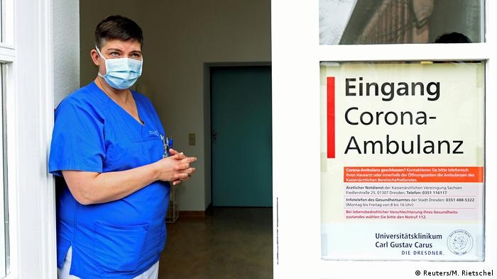 A medical worker in a face masks stands outside a clinic dedicated to coronavirus treatment (Reuters/M. Rietschel)