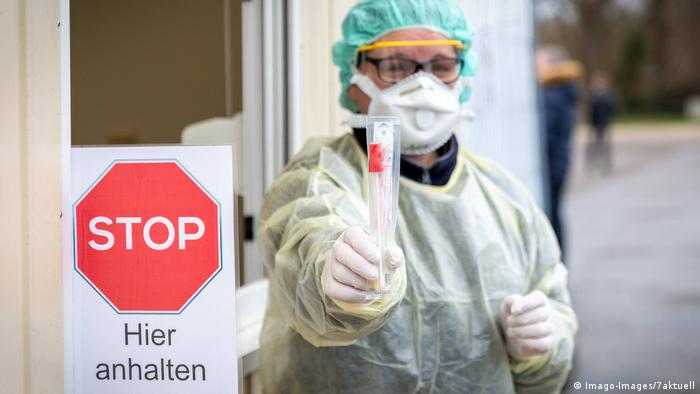A tester holds out a coronavirus test tube next to a stop sign (Imago-Images/7aktuell)