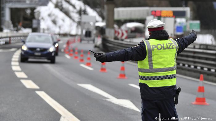 Полицейский останавливает автомобили на перевале Бреннер с австрийской стороны