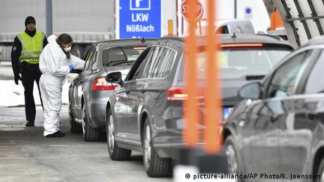 Медицинский работник на границе Австрии с Италией измеряет температуру водителю автомобиля из Италии.