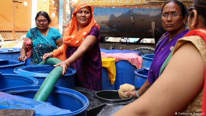 Women collecting water in giant containers