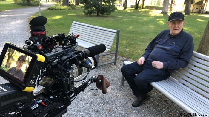 Hermann Lüdeking sitzt auf einer Bank und wird gefilmt