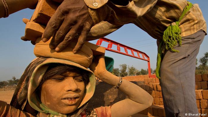 Woman carrying heavy load at construction site in India