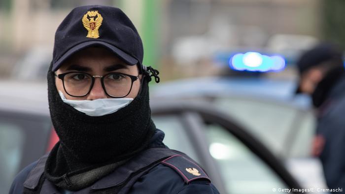Un policía italiano con una máscara de respiración.