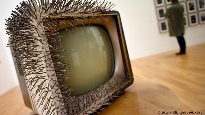 Old television set with Nails driven into three sides around the screen at the front