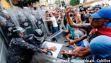 10.03.2020, Venezuela, Caracas: Anhänger der Opposition schlagen auf Sicherheitskräfte und ziehen an einem Schutzschild während eines Protests gegen die Regierung von Präsident Maduro. Oppositionsführer Guaido hatte zu den Protesten und zur Forderung freier Präsidentschaftswahlen aufgerufen. Foto: Ariana Cubillos/AP/dpa +++ dpa-Bildfunk +++