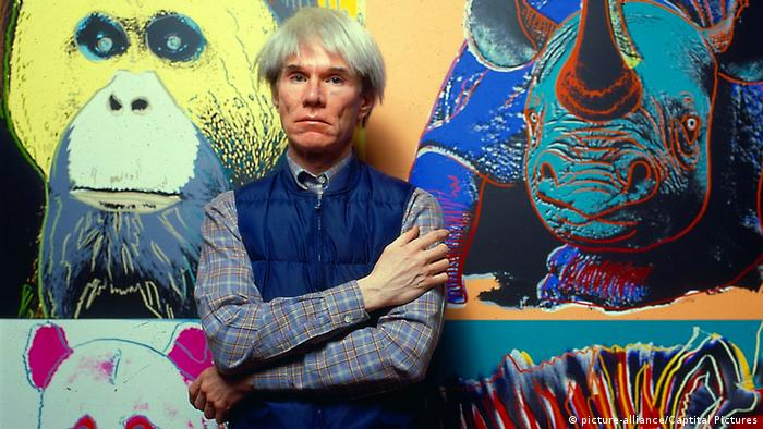 Colorful photograph of pop artist Andy Warhol posed standing in front of a large piece of art. (picture-alliance/Captital Pictures)