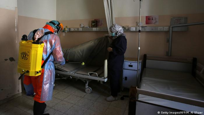 A member of a Palestinian health team in protective gear disinfects a patient's bed at Beit Jala Hospital
