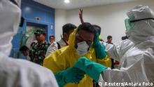 Indonesien | Medizinische Angestellte tragen Sicherheitsanzüge vor evakuierung der Crew der Diamond Princess