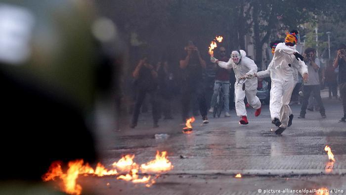 Manifestantes mascarados protestam contra o governo no Chile