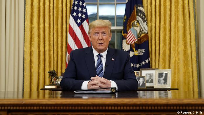 Donald Trump sentado atrás de uma mesa, com a bandeira dos Estados Unidos ao fundo.