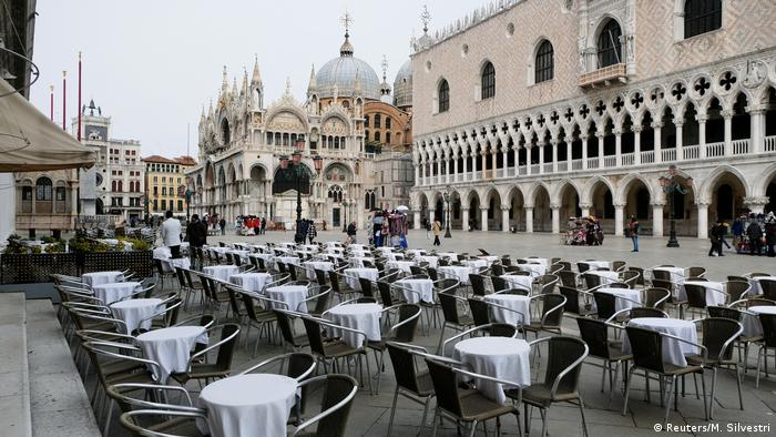 Empty tables are pictured outside a restaurant at St Mark's Square, which is usually full of tourists