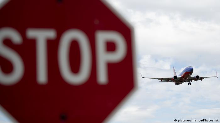 A stop sign and a plane approaching to land at Ronald Reagan Washington National Airport in Arlington, Virginia