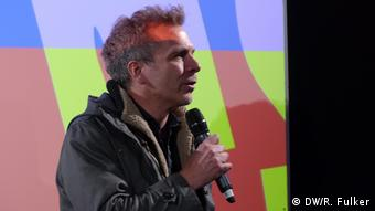 Dirk Kaftan, in a jacket, holds a microphone and gives a speech in front of a colorful, abstract backdrop