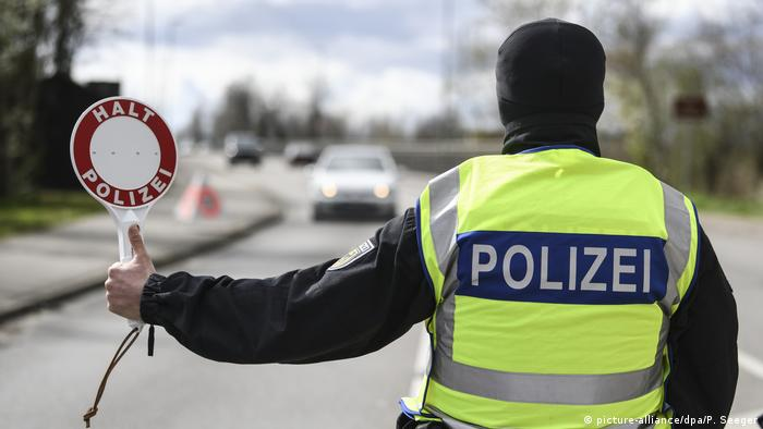 A policeman with a stop sign (picture-alliance/dpa/P. Seeger)
