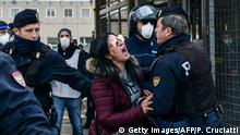 Police officers hold off an inmate's relative shouting in protest outside the SantAnna prison in Modena, Emilia-Romagna, in one of Italy's quarantine red zones on March 9, 2020. - Inmates in four Italian prisons have revolted over new rules introduced to contain the coronavirus outbreak, leaving one prisoner dead and others injured, a prison rights group said on March 8. Prisoners at jails in Naples Poggioreale in the south, Modena in the north, Frosinone in central Italy and at Alexandria in the northwest had all revolted over measures including a ban on family visits, unions said. (Photo by Piero CRUCIATTI / AFP) (Photo by PIERO CRUCIATTI/AFP via Getty Images)